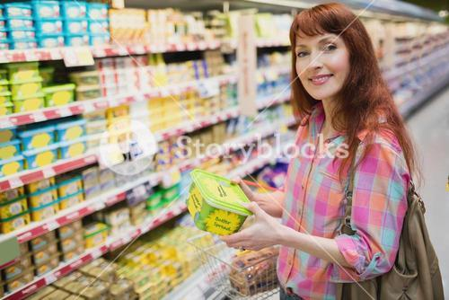 Woman smiling at camera while holding product