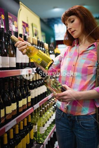 Woman hesitating between two bottles of wine