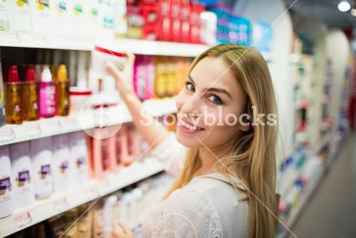 Smiling blonde woman posing while picking a product