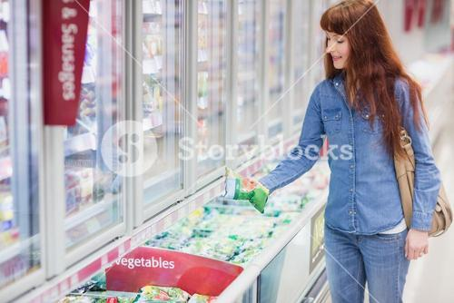 Woman buying vegetables in frozen section