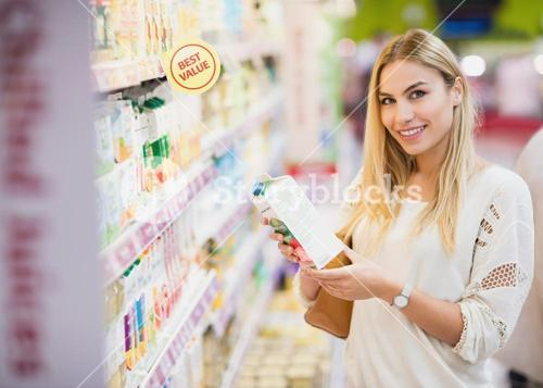 Smiling customer looking at a bottle of fruit juice