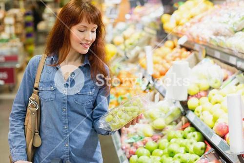 Smiling customer holding a box of grapes