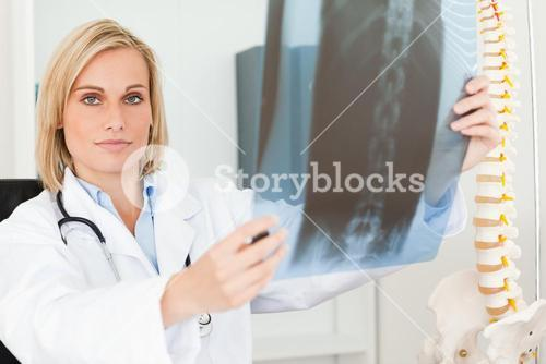 Serious doctor looking at xray looks into camera