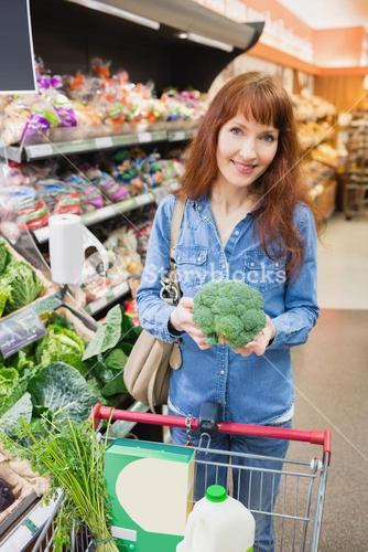 Smiling customer holding a broccoli