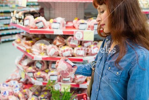 Customer picking a peace of meat in a supermarket