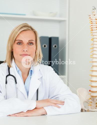 Serious doctor with model spine next to her looks into camera