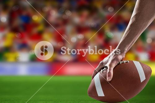 Composite image of man holding a american football ball