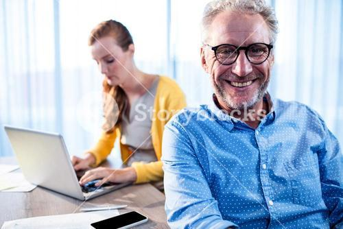 Smiling businessman and concentrated businesswoman