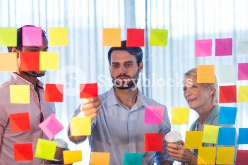 Business people looking at sticky notes on the wall