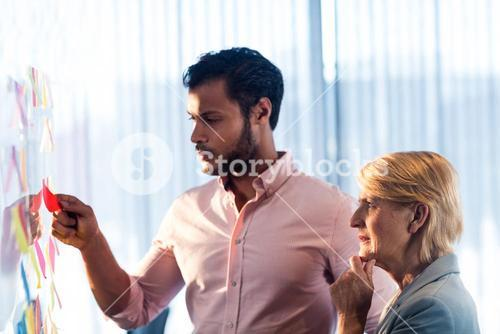 Side view of two business people looking at post it wall