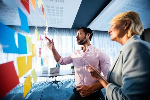 Side view of two business people looking at sticky notes wall