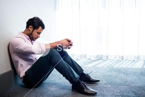 Depressed businessman sitting against a wall and looking down