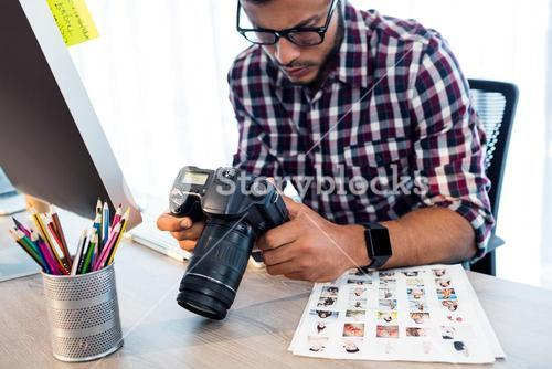 Side view of photographer working at desk
