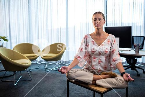 Businesswoman doing yoga
