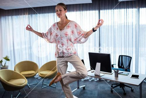 Businesswoman doing yoga on a table