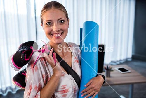 Casual businesswoman with yoga mat and sports shoes