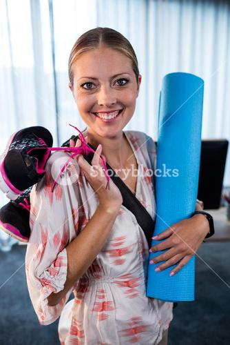 Casual business woman with yoga mat and sports shoes