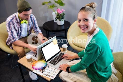 Coworkers using laptop