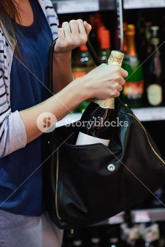 Woman putting a wine bottle in her bag