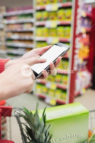 Focus on foreground of woman touching her mobile phone