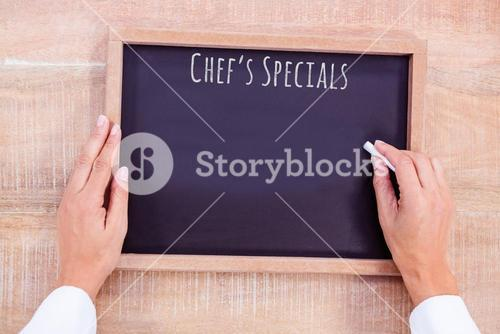 Composite image of chef hand writing on a chalkboard