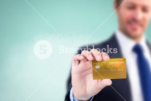 Composite image of businessman showing a creditcard