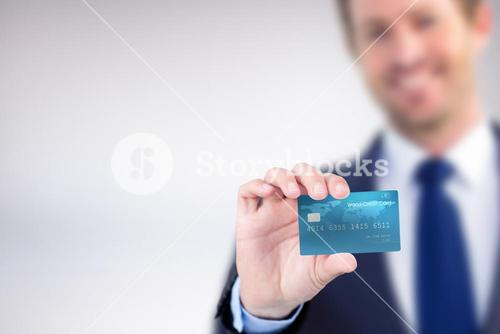 Composite image of happy businessman showing a creditcard