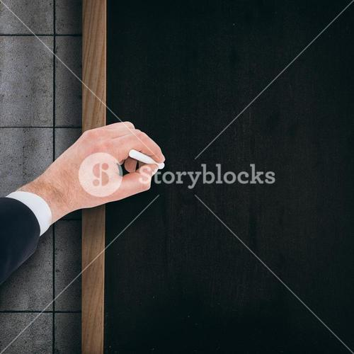 Composite image of hand of businessman writing with a white chalk