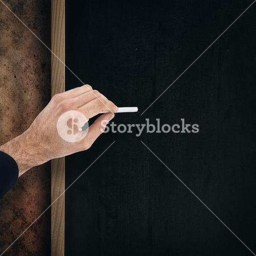 Composite image of hand of a businessman writing with a white chalk