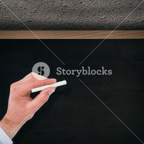 Composite image of businessman writing with white chalk