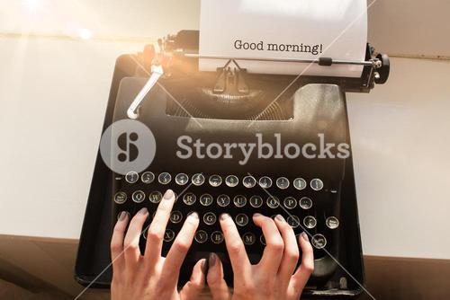 Good morning! against womans hand typing on typewriter