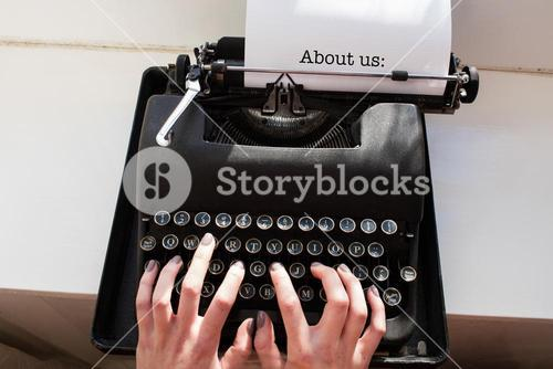 About us: against womans hand typing on typewriter