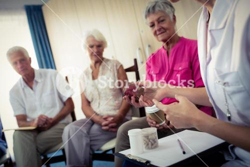 Seniors talking with nurse about medication