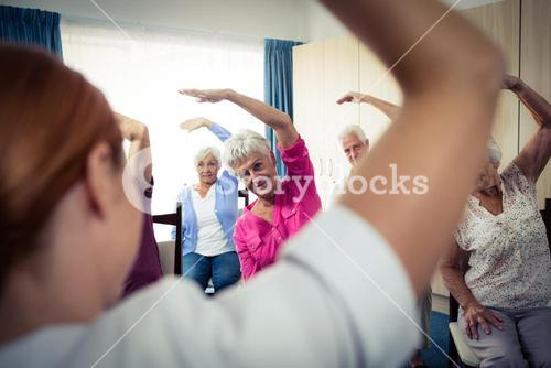 Group of seniors doing exercises with nurse