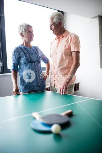 Couple of seniors interacting behind a ping pong table