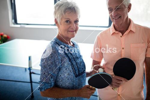 Portrait of a couple of seniors front of a ping pong table