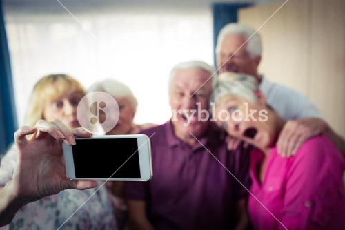 Group of seniors doing a selfie with a smartphone and funny faces