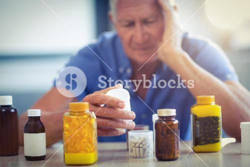 Senior man suffering from headache with prescription bottle