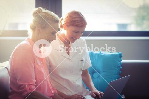 Female nurse and senior woman using laptop