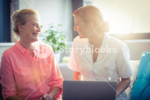 Female nurse and senior woman smiling while using laptop