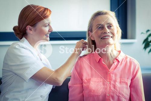 Female nurse combing hair of senior woman