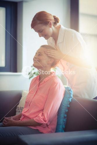 Female nurse giving head massage to woman