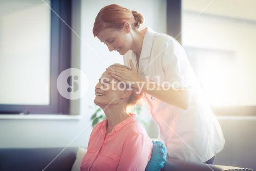 Nurse giving head massage to woman