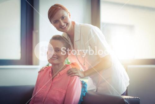 Portrait of happy nurse and patient in living room
