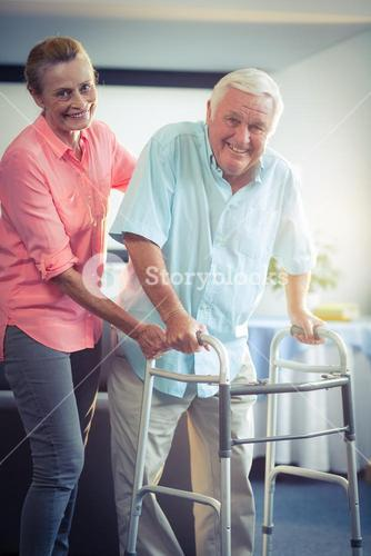Senior woman helping senior man to walk with walker