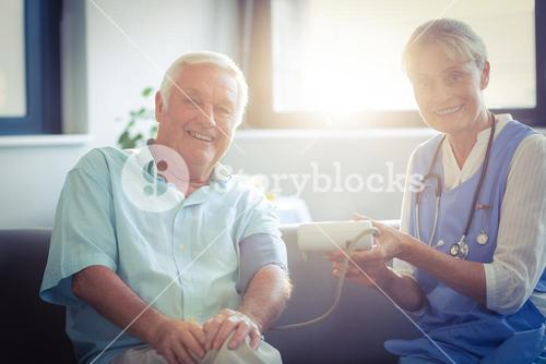 Female doctor checking blood pressure of senior man