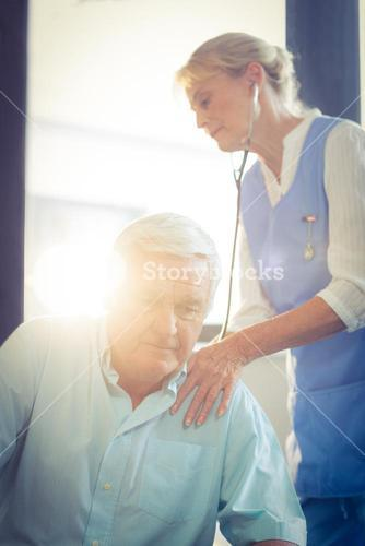 Female doctor examining a senior man