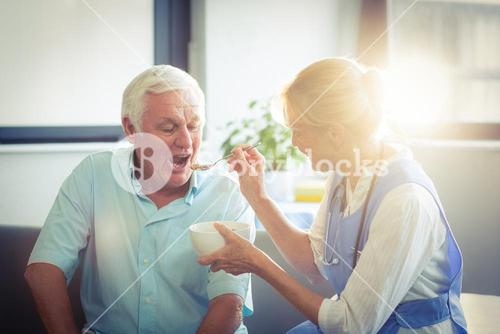 Female doctor feeding senior man