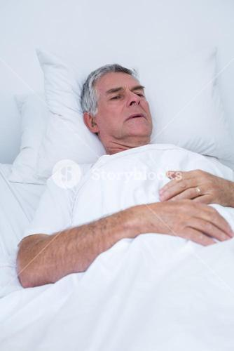 Senior man lying on bed