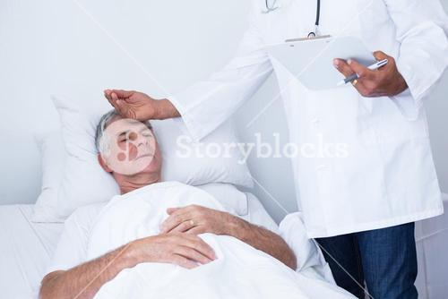 Male doctor examining senior man